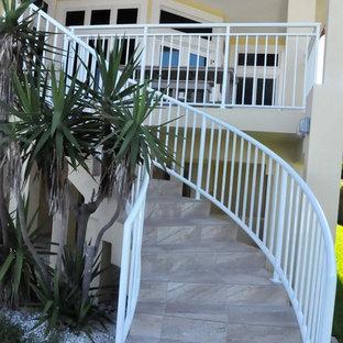 タンパの大きいタイルのおしゃれなサーキュラー階段 (金属の手すり、タイルの蹴込み板) の写真
