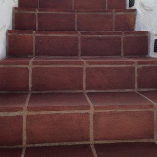 オレンジカウンティの大きいタイルの地中海スタイルのおしゃれな直階段 (タイルの蹴込み板) の写真