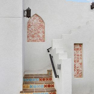 ロサンゼルスの中サイズのタイルの地中海スタイルのおしゃれなかね折れ階段 (タイルの蹴込み板、混合材の手すり) の写真
