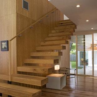 Immagine di una scala sospesa minimalista con pedata in legno, nessuna alzata e parapetto in legno
