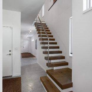 Diseño de escalera suspendida, actual, con escalones de madera, contrahuellas de madera pintada y barandilla de metal