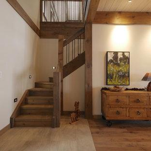 他の地域の大きい木のラスティックスタイルのおしゃれなかね折れ階段 (木の蹴込み板、木材の手すり) の写真