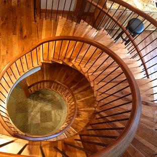 Immagine di una grande scala a chiocciola rustica con pedata in legno, alzata in legno e parapetto in legno