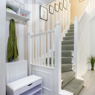 Inspiration for a transitional painted l-shaped wood railing staircase remodel in London with painted risers