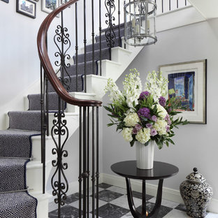 Medium sized classic painted wood curved staircase in London with painted wood risers.