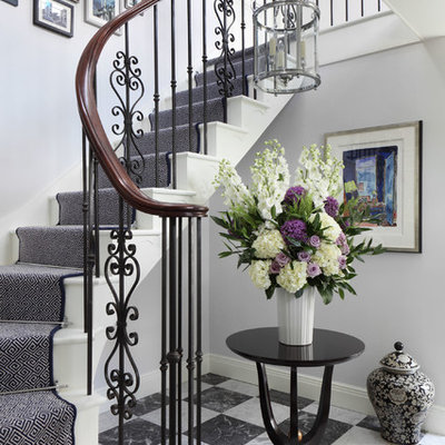 Mid-sized elegant painted curved staircase photo in London with painted risers