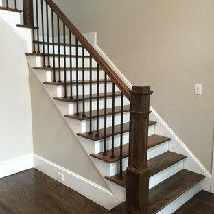Imagen de escalera en L, tradicional, de tamaño medio, con escalones de madera, contrahuellas de madera pintada y barandilla de varios materiales