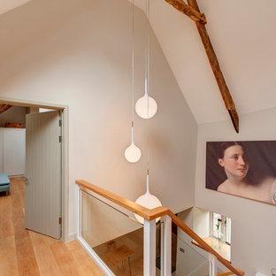 Farmhouse wooden l-shaped glass railing staircase photo in Devon