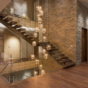 Ejemplo de escalera en L, contemporánea, sin contrahuella, con escalones de madera y barandilla de vidrio