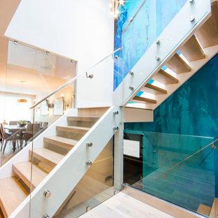 Ejemplo de escalera en L y papel pintado, contemporánea, sin contrahuella, con escalones de madera, barandilla de vidrio y papel pintado