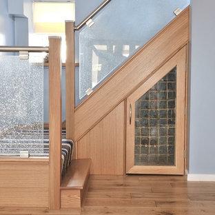 Imagen de escalera curva, contemporánea, de tamaño medio, con escalones de vidrio, contrahuellas de madera y barandilla de metal