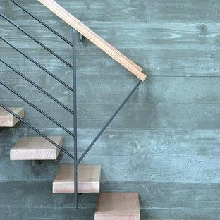 Esempio di una scala sospesa minimalista con pedata in legno