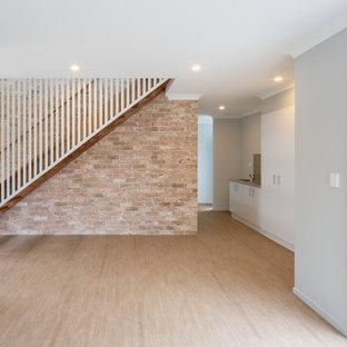 Inspiration pour un grand escalier droit marin avec des marches en bois, des contremarches en bois, un garde-corps en bois et un mur en parement de brique.