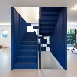 Design ideas for a contemporary painted wood u-shaped metal railing staircase in London with painted wood risers.