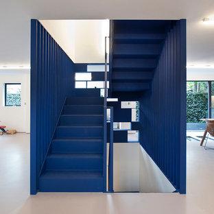 ロンドンのフローリングのコンテンポラリースタイルのおしゃれな折り返し階段 (フローリングの蹴込み板、金属の手すり) の写真