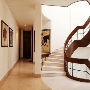 Diseño de escalera curva, de estilo zen, con escalones con baldosas, contrahuellas con baldosas y/o azulejos y barandilla de madera