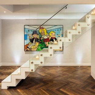 Imagen de escalera recta, actual, de tamaño medio, con escalones de mármol, contrahuellas de mármol y barandilla de vidrio
