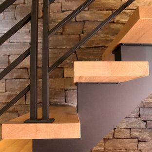 Immagine di una scala sospesa stile rurale di medie dimensioni con pedata in legno, nessuna alzata e parapetto in metallo