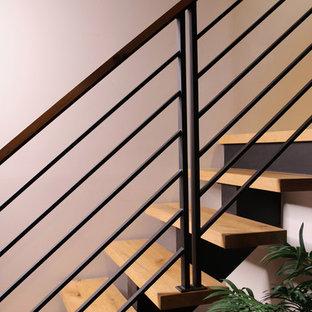 Ejemplo de escalera suspendida, rústica, de tamaño medio, sin contrahuella, con escalones de madera y barandilla de metal