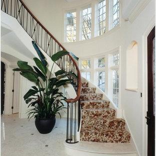 Cette image montre un très grand escalier courbe traditionnel avec des marches en moquette et des contremarches en moquette.