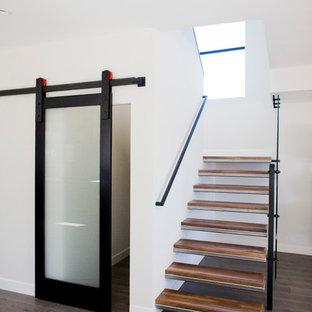 Ejemplo de escalera suspendida, minimalista, sin contrahuella, con escalones de metal
