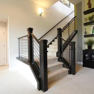 Klassisk inredning av en stor l-trappa, med heltäckningsmatta, sättsteg med heltäckningsmatta och räcke i trä