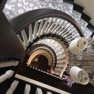 ニューヨークの大きい木のトラディショナルスタイルのおしゃれなサーキュラー階段 (フローリングの蹴込み板) の写真