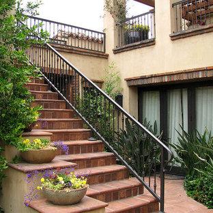 Ejemplo de escalera recta, de tamaño medio, con escalones de terracota, contrahuellas de terracota y barandilla de metal