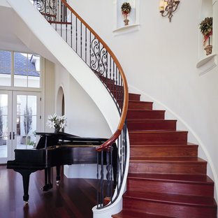 Example of a classic wooden curved staircase design in Charleston with wooden risers