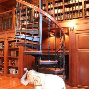 Ispirazione per una piccola scala a chiocciola classica con pedata in legno e nessuna alzata