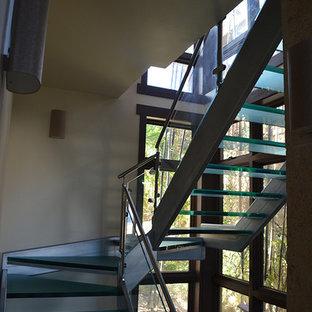 """Ispirazione per una scala a """"L"""" costiera di medie dimensioni con pedata in vetro, nessuna alzata e parapetto in vetro"""