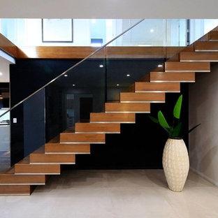 Diseño de escalera recta, contemporánea, con escalones de madera, contrahuellas de madera y barandilla de vidrio