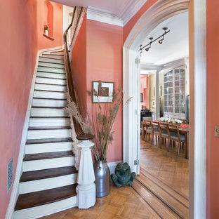 Diseño de escalera curva, clásica, pequeña, con escalones de madera, contrahuellas de madera pintada y barandilla de madera