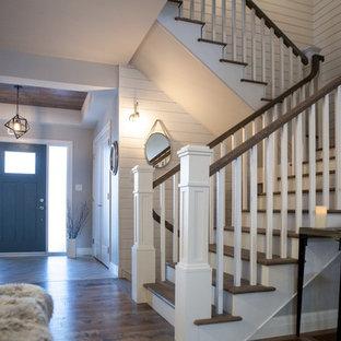 Ejemplo de escalera en L, de estilo americano, extra grande, con escalones de madera y contrahuellas de madera pintada