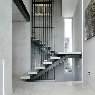 """Immagine di una scala a """"U"""" design con pedata in cemento e nessuna alzata"""