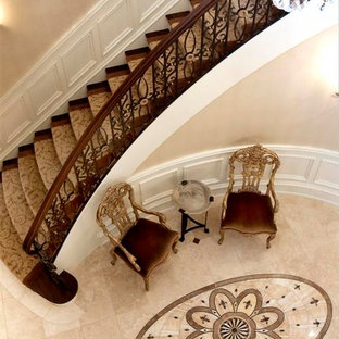 Example of a large classic wooden curved staircase design in Chicago with painted risers