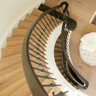 Diseño de escalera curva, mediterránea, con escalones de madera, contrahuellas de madera y barandilla de varios materiales