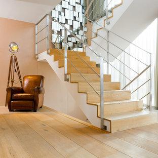 Cette image montre un grand escalier design en U avec des marches en bois et des contremarches en bois.
