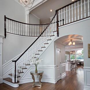 Idée de décoration pour un escalier courbe de taille moyenne avec des marches en bois, des contremarches en bois, un garde-corps en bois et du lambris.