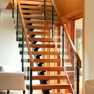 Ejemplo de escalera recta, moderna, sin contrahuella, con escalones de madera y barandilla de vidrio