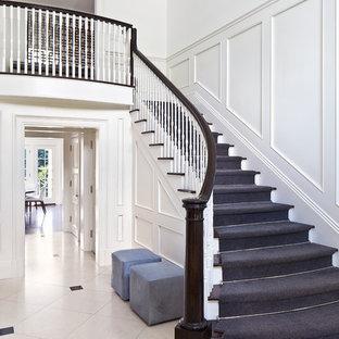 Imagen de escalera curva, tradicional renovada, de tamaño medio, con barandilla de madera, escalones de madera y contrahuellas de madera pintada