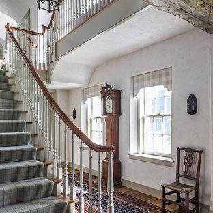 Imagen de escalera en U, de estilo de casa de campo, extra grande, con escalones de madera y contrahuellas de madera pintada