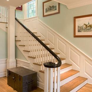 Modelo de escalera en L, clásica, grande, con escalones de madera, contrahuellas de madera pintada y barandilla de madera