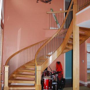 Diseño de escalera curva, de estilo americano, de tamaño medio, con escalones de madera y contrahuellas de madera