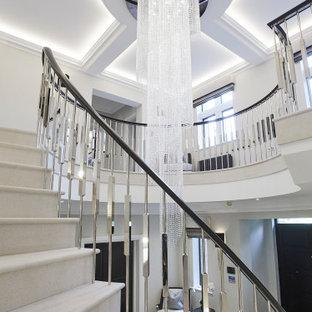 チェシャーの巨大なライムストーンのモダンスタイルのおしゃれなサーキュラー階段 (ライムストーンの蹴込み板、金属の手すり) の写真
