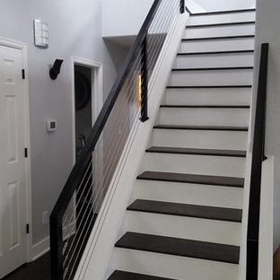 Esempio di una scala a rampa dritta minimalista di medie dimensioni con pedata in legno, alzata in legno verniciato e parapetto in cavi