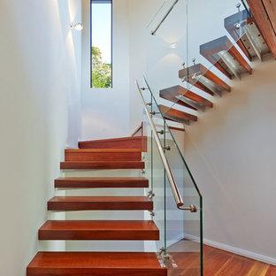 Foto de escalera suspendida, contemporánea, sin contrahuella, con escalones de madera y barandilla de vidrio