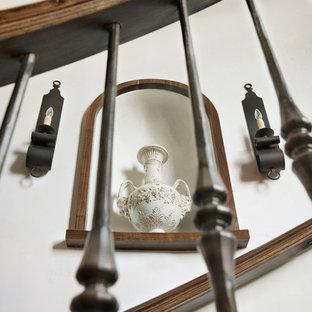 Immagine di una grande scala a chiocciola mediterranea con pedata in legno e alzata in legno
