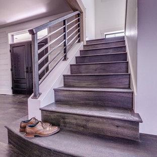 シアトルの中サイズの木のインダストリアルスタイルのおしゃれなかね折れ階段 (木の蹴込み板、金属の手すり) の写真