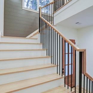 Idée de décoration pour un grand escalier champêtre en U avec des marches en bois, des contremarches en bois peint, un garde-corps en bois et du lambris.